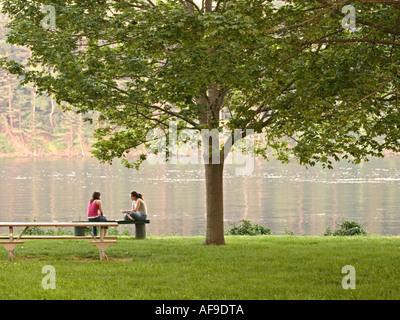 Zwei Mädchen sitzen unter Schattenspender - Stockfoto