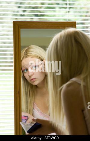 Ein junges Mädchen ihr Gesicht im Spiegel überprüfen und Schminken - Stockfoto