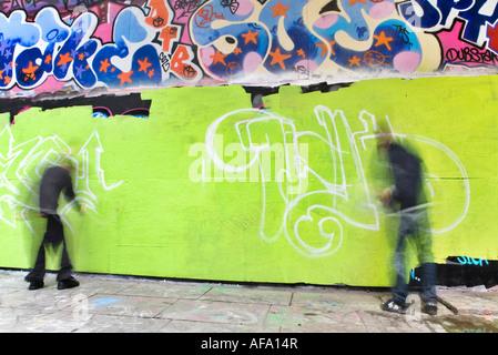 Graffiti-Künstler malen ihren Tag an der Wand - Stockfoto