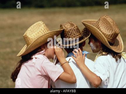 Drei Kinder in Strohhüte sagen einander Geheimnisse - Stockfoto