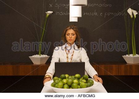 Junge Frau sitzt vor einem laptop - Stockfoto