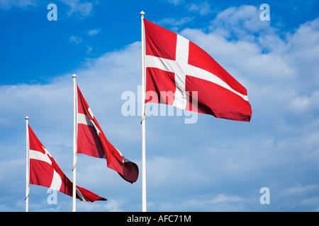Dänische Flaggen vor blauem Himmel mit Wolken - Stockfoto