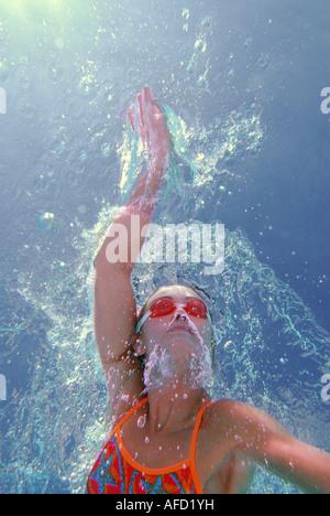 Eine sportliche junge Frau sieht man Freestyle von unter Wasser schwimmen, wie sie im Außenpool runden schwimmt. - Stockfoto