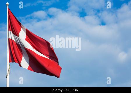 Dänische Flagge vor einem blauen Himmel mit Wolken - Stockfoto