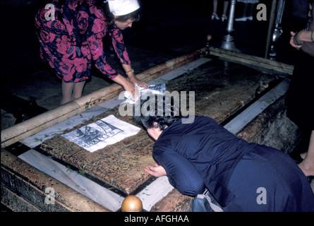 Pilger, die die Stein von der Salbung in der Heilig-Grab-Kirche, Jerusalem küssen - Stockfoto