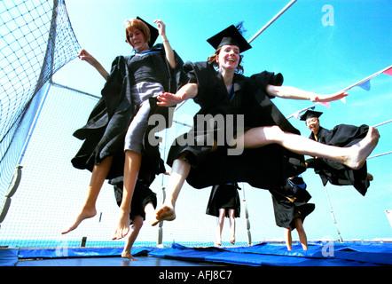 Studenten feiern Abschlusstag auf einem Trampolin - Stockfoto