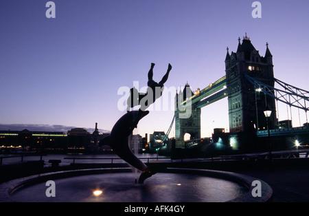 Der Delphin mit einer Boy-Statue am Ufer der Themse neben der Tower Bridge in London - Stockfoto