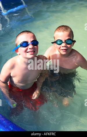 Zwei Brüder im Pool mit Schwimmbrillen - Stockfoto