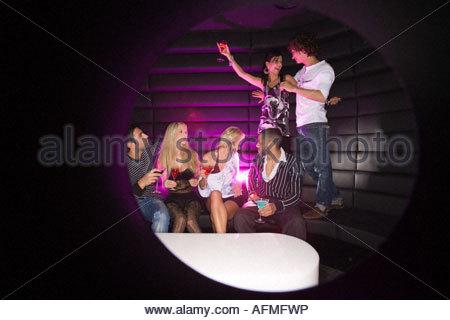 Junge Paare tanzen in einem Nachtclub mit ihren Freunden einen Drink - Stockfoto