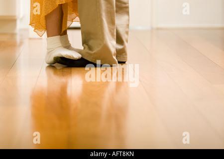 Tochter steht auf Vaters Füße, tanzen in Küche - Stockfoto