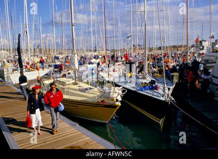 Paare, die am Steg neben Marina voller Segelboote bei Cowes Regatta Isle Of Wight. - Stockfoto