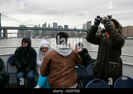 weibliche Touristen verwendet eine Point and Shoot Kamera mit kalten Touristen auf der Rückseite von einem Kreuzfahrt - Stockfoto