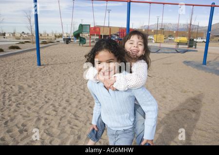 Mädchen, das Huckepack-Fahrt für Schwester auf Spielplatz - Stockfoto