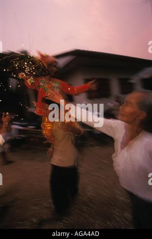 Frau werfen Reis in einem ihrer großen Enkel während Poy Sang lange die Weihe von Novizen Thailand Mae Hong Son - Stockfoto