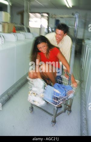 Junges Paar wird spielerisch beim Wäschewaschen an öffentlichen Waschsalon in Kalifornien gesehen - Stockfoto
