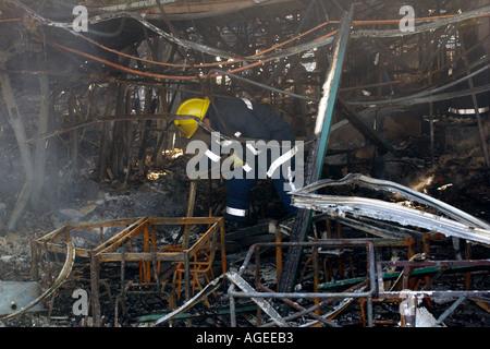 Feuerwehrmann Sichtung durch die verworrenen verkohlten Überreste eines Klassenzimmers nach einem Brand Rogerstone - Stockfoto