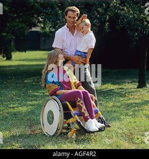 Behinderte Frau im Rollstuhl mit Mann und kleiner Junge im Garten - Stockfoto