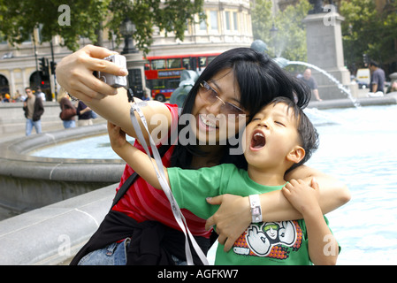 Eine chinesische Familie junge und Mutter touristischen posiert für Selbstporträt auf dem Trafalgar Square in London, - Stockfoto