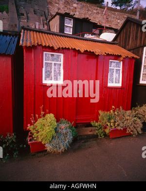 Eine Hütte, Wohnung rot mit Blume Tröge außerhalb und mit einer Mauer im Hintergrund das Haus hat ein Dach aus Blech - Stockfoto
