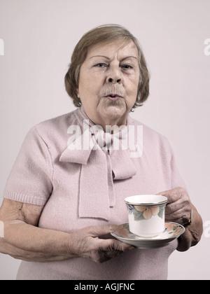 Frau mit einer Teetasse und Untertasse - Stockfoto