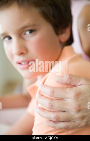 Junge mit Mutter die Hand auf seiner Schulter - Stockfoto