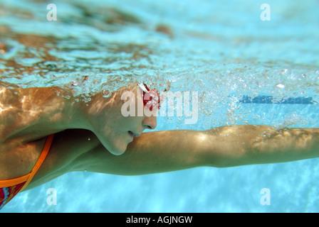 Eine junge Frau wird von Unterwasser schwimmt Freestyle dabei Runden in einem klaren Pool gesehen. - Stockfoto