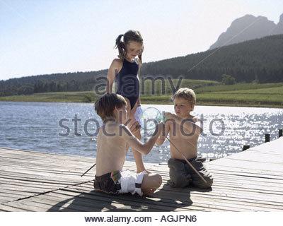 Geschwister spielen auf einem pier - Stockfoto