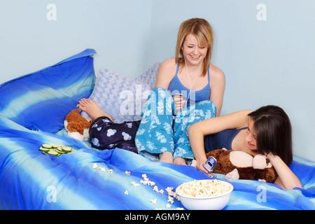 Zwei Mädchen sitzen auf Bett - Stockfoto