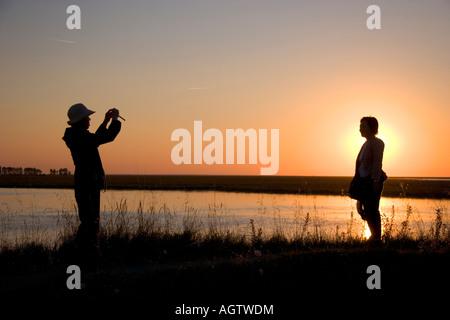 Touristen, die mit dem Fotografieren einer Frau bei Sonnenuntergang in der Nähe von Le Mont Saint Michel in der - Stockfoto