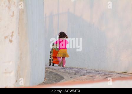 Kleine Mädchen schieben Kinderwagen auf Bürgersteig - Stockfoto