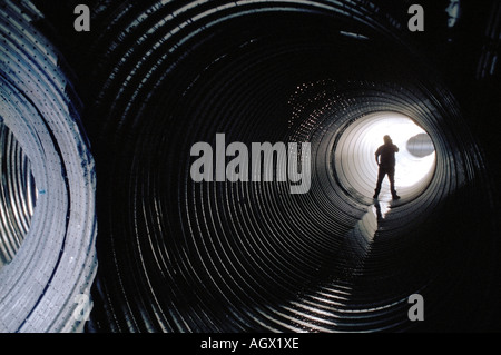 Ein Bauarbeiter ist in einem Wasserrohr Tunnel Silhouette. - Stockfoto