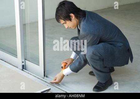 Mann im Anzug Messungen neben Glas-Schiebetür - Stockfoto