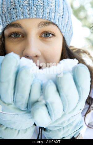Teenager-Mädchen essen Schnee aus Handschuhen, Blick in die Kamera, Nahaufnahme - Stockfoto