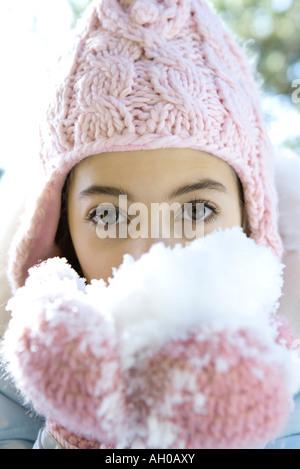 Preteen Mädchen essen Schnee aus Händen gefesselt, Blick in die Kamera - Stockfoto