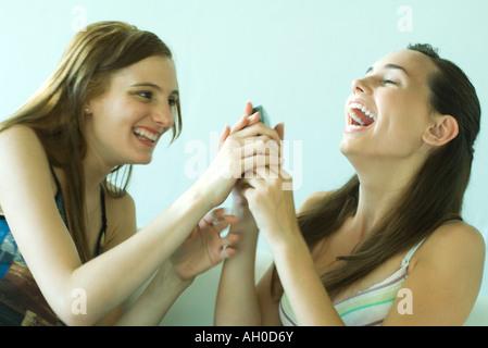 Zwei junge Freunde lachen zusammen, eine Einnahme-Telefon von der anderen, verschwommene Bewegung - Stockfoto