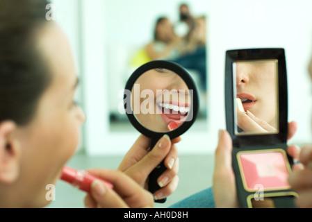 Zwei junge Freunde Auftragen von Lippenstift, betrachtet man selbst in der hand Spiegel, beschnitten Ansicht - Stockfoto