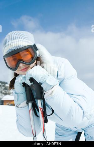 Teengirl stützte sich auf Ski-Stöcke, lächelnd in die Kamera - Stockfoto