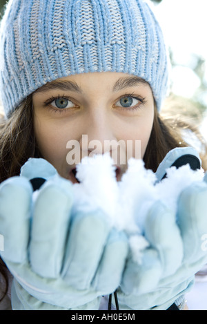 Teenager-Mädchen essen Schnee, Hände, Blick in die Kamera - Stockfoto