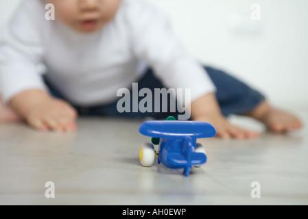 Spielzeugflugzeug auf Boden, Baby im Hintergrund - Stockfoto