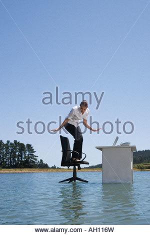 Eine Frau auf ihrem Bürostuhl auf Wasser - Stockfoto
