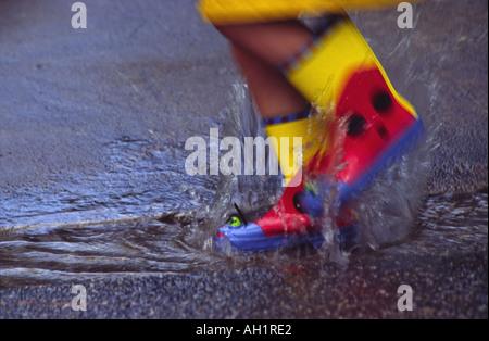 Nahaufnahme eines Kindes in bunten Regenstiefel oder Gummistiefel in einer Pfütze auf der Straße durch Spritzwasser - Stockfoto