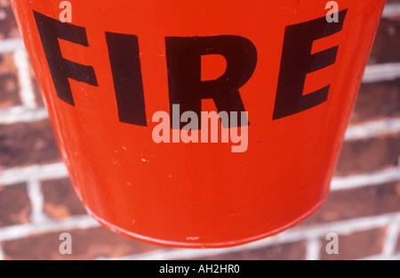 Nahaufnahme von einem hellen Rot Aluminium-Eimer mit fetten schwarzen Buchstaben besagt Feuer ausgesetzt auf einer dunklen Ocker Ziegelmauer