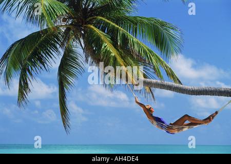 Frau in Hängematte unter Palmen entspannen - Stockfoto