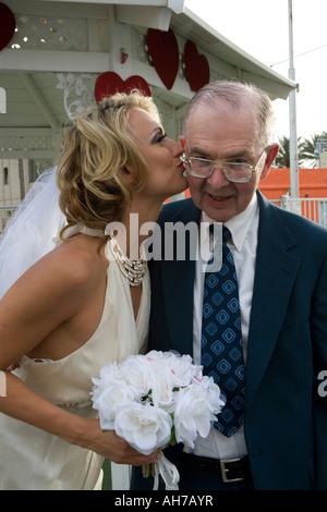 Braut, die einen älteren Mann auf die Wange küssen - Stockfoto