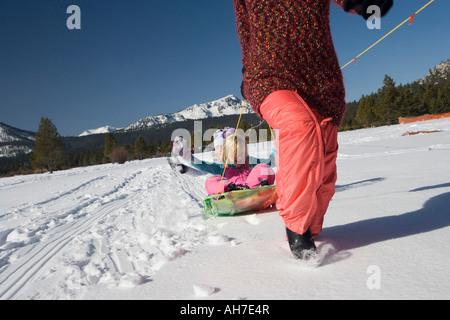 Reife Frau, die ihren Töchtern auf einem Schlitten ziehen - Stockfoto