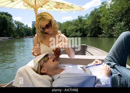 Junge Frau sitzt in einem Boot Fütterung Trauben mit einem jungen Mann auf ihrem Schoß - Stockfoto