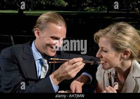 Junger Mann Fütterung Sushi, eine junge Frau mit Stäbchen und lächelnd - Stockfoto