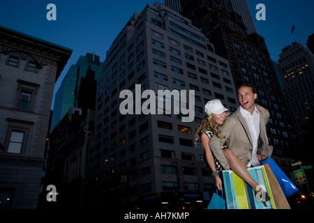 Niedrigen Winkel Ansicht einer jungen Frau Reiten Huckepack auf einem jungen Mann und lächelnd, New York City, New - Stockfoto