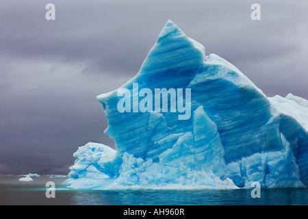 Große schöne klassische blaue Spitzen Eisberg als finden Sie in der Regel unter Narsaq mit regnerischen grauen Himmel - Stockfoto