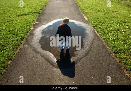 kleiner Junge blickte auf Pfütze und Schatten entlang einem Gehweg - Stockfoto